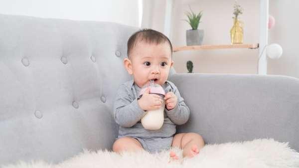 طفل يحمل زجاجة الرضاعة